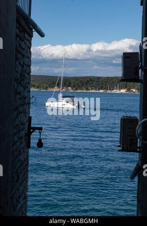 Yacht moving in sea as seen through buildings, Rovinj, Istria, Croatia - Stock Photo