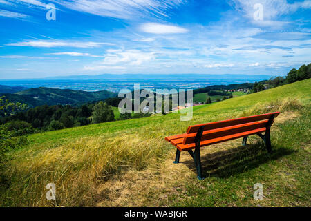 Germany, Orange wooden bench on top of a mountain with fantastic view over endless valley and black forest nature landscape