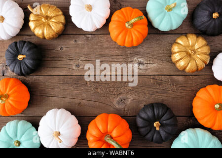 Autumn frame of various colorful pumpkins on a rustic wood background. Top view with copy space. - Stock Photo