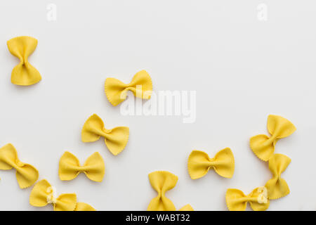Italian raw multicolored farfalle pasta on white background with copy space.Colorful pasta in bow tie shape. Italian cuisine concept. Mockup. - Stock Photo