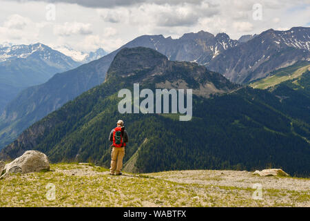 A hiker with a red backpack admiring the mountain landscape of the Mont Blanc massif in the Italian Alps in summer, Courmayeur, Aosta Valley, Italy - Stock Photo
