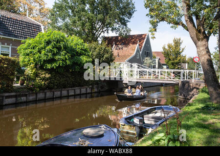 BROEK IN WATERLAND, NETHERLANDS - SEPTEMBER 1, 2018: Scenic view Broek in Waterline in North Holland with architecture and people rowing on the canal. - Stock Photo