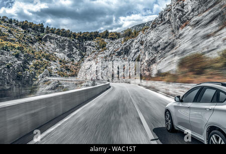 Highway among the mountain scenery. White car on a mountain road. - Stock Photo