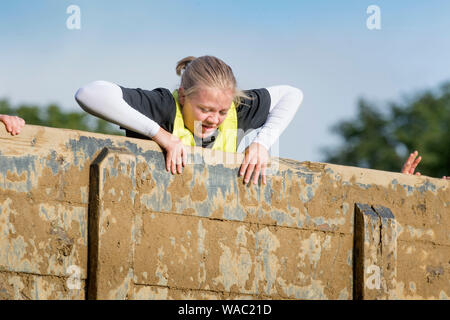 A girl negotiates the 'Hero Walls' at the Tough Mudder endurance event in Badminton Park, Gloucestershire UK - Stock Photo