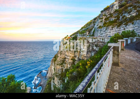 View from a stop along the road on the Amalfi Coast near Sorrento with a luxury villa perched high on a cliff with the sea and tide pools below - Stock Photo