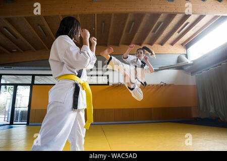 Two young women in white kimonos attacking and fighting. - Stock Photo
