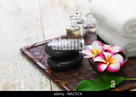 tropical spa resort concept; plumeria, hot stones, towels, and massage oils - Stock Photo