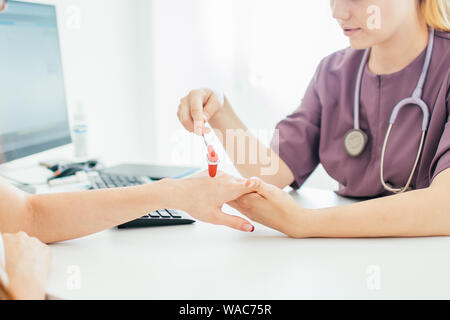 Neurological examination. The neurologist testing hand reflexes on a female patient using a hammer. Diagnostic, healthcare, medical service. - Stock Photo