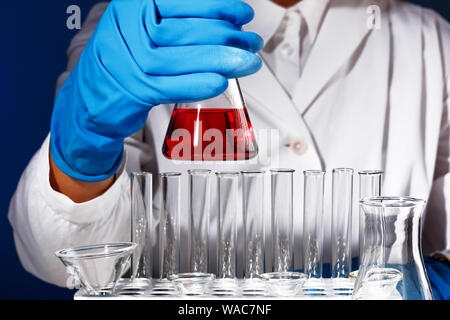 In a chemistry lab, a man is a pharmacist analyzing a flask with red liquid. Medical experiment with a tube. Chemist working on a test with blue glove - Stock Photo