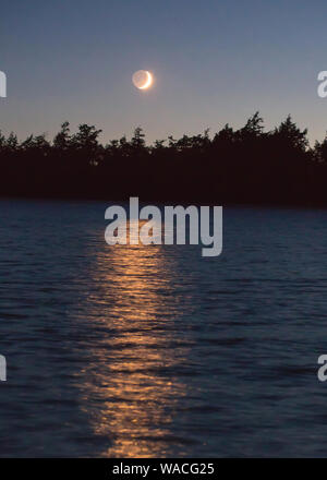 A crescent moon illuminated by the setting sun casts a golden glow over a northern Wisconsin lake. - Stock Photo