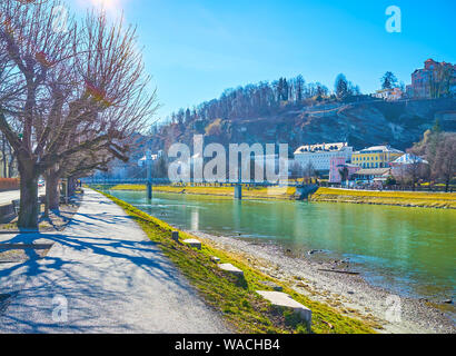 The cozy promenade of Salzach river with winter bare trees and splendid medieval town on the other bank of the river, Salzburg, Austria - Stock Photo