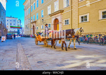 SALZBURG, AUSTRIA - FEBRUARY 27, 2019: The tourists in the carriage ride along old streets in Altstadt, enjoying magnificent architecture of medieval - Stock Photo