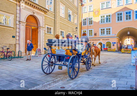 SALZBURG, AUSTRIA - FEBRUARY 27, 2019: Tourists enjoy the city tour in old style horse drawn carriage, riding along the old edifices of Churfurststras - Stock Photo