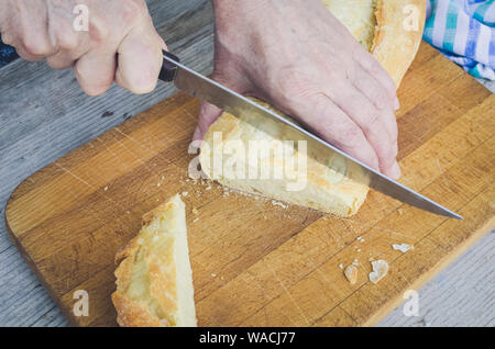 Senior woman cutting freshly baked bread on the wooden board on the rural kitchen table. Traditional bakery concept. Rustic vintage style. - Stock Photo