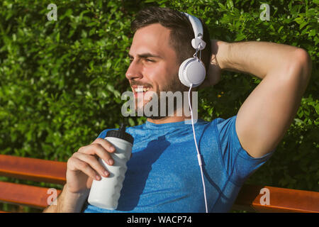 Handsome man with headphones  drinking water and resting after exercise in the park. - Stock Photo