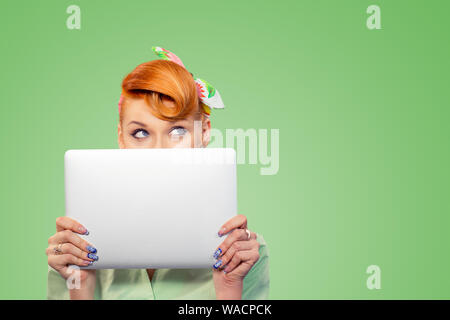 Student hiding behind a laptop. Closeup portrait headshot beautiful confident young businesswoman pinup girl holding computer isolated on green backgr - Stock Photo
