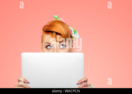 Student hiding behind laptop. Closeup portrait headshot beautiful confident young business woman pinup girl holding computer isolated peach pink color - Stock Photo
