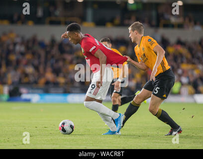 19th August 2019; Molineux Stadium, Wolverhampton, West Midlands, England; English Premier League, Wolverhampton Wanderers versus Manchester United; Ryan Bennett of Wolverhampton Wanderers pulls back on the shirt of Anthony Martial of Manchester United as he breaks forward with the ball is at his feet - Strictly Editorial Use Only. No use with unauthorized audio, video, data, fixture lists, club/league logos or 'live' services. Online in-match use limited to 120 images, no video emulation. No use in betting, games or single club/league/player publications - Stock Photo
