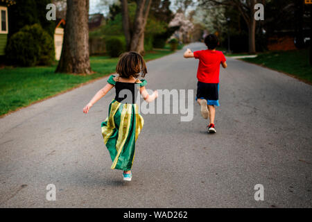 two children skip happily down a tree-lined street in springtime - Stock Photo