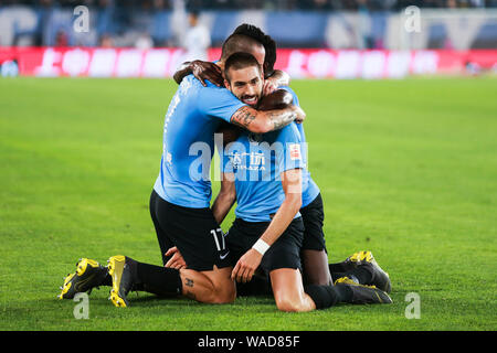 Belgian football player Yannick Ferreira Carrasco, center, of Dalian Yifang celebrates with Ghanaian football player Emmanuel Okyere Boateng and Slova - Stock Photo