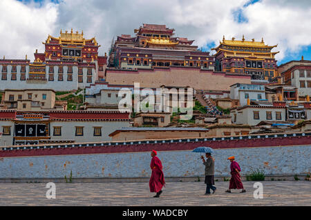 Tibetan monks walking in front of the Songzanlin monastery, also known as Ganden Sumtseling Gompa in Zhongdian, Shangri La, Yunnan province, China. - Stock Photo