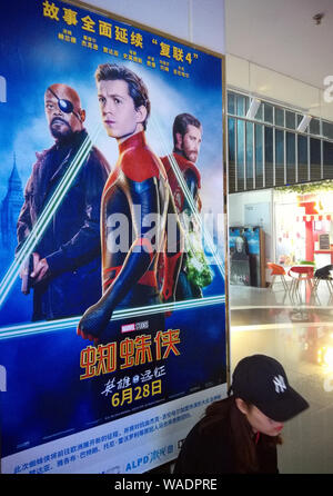 --FILE--A filmgoer waits in front of a poster of American superhero film 'Spider-Man: Far from Home' at a cinema in Yichang city, central China's Hube - Stock Photo