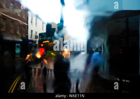 Passenger's view of blurry pedestrians out of bus window on wet rainy day with water running down the bus window pane - Stock Photo