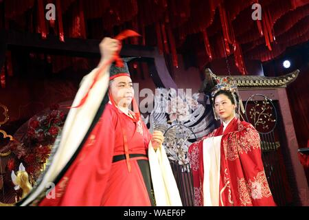 Anhui, Anhui, China. 20th Aug, 2019. Anhui, CHINA-A ''splendid'' Chinese wedding ceremony is successfully held in the grand banquet hall of Huayi hotel in Wuhu, Anhui province, Aug. 17, 2019.The theme of the Chinese wedding show highlights the Chinese wedding customs, attracting more than 100 couples and many wedding brands invited to participate in the scene, beautiful models wearing beautiful bridal suits on the runway very beautiful eyes. Credit: SIPA Asia/ZUMA Wire/Alamy Live News - Stock Photo