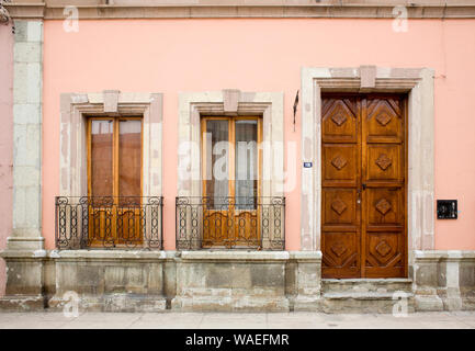 Spanish colonial building exterior with carved wooden door, casement windows and wrought iron railings, Oaxaca City, Oaxaca, Mexico local architecture - Stock Photo