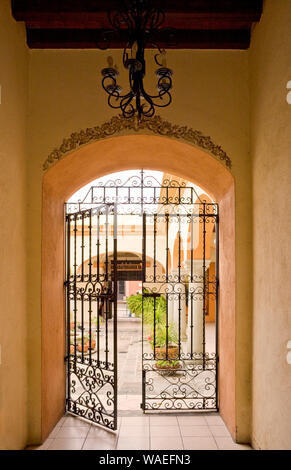 View through open wrought iron gate to beautiful courtyard garden, Oaxaca City, Oaxaca, Mexico Spanish colonial architecture - Stock Photo