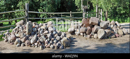 Two large piles of granite boulders and stones lie in forest near a village fence - Stock Photo