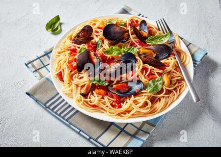 close-up of pasta with mussels in a Spicy Tomato Sauce and basil leaves on a white plate on a white concrete table, horizontal view from above, - Stock Photo