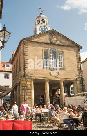People eating at an outdoor cafe in Whitby market place, North Yorkshire, England, UK - Stock Photo