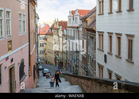 Few tourists at the stairs to the Prague Castle and old buildings along the Thunovska street at the Mala Strana (Lesser Town) district in Prague. - Stock Photo