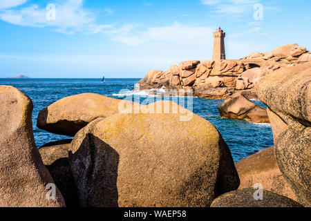The Ploumanac'h lighthouse, named Mean Ruz, on the Pink Granite Coast in Perros-Guirec, northern Brittany, with large granite rocks in the foreground. - Stock Photo