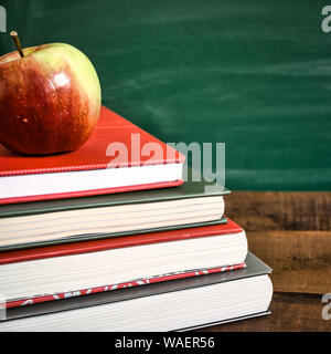 Books and apple on wooden table in front of the school chalkboard. Back to school concept. Vintage toned photo. - Stock Photo