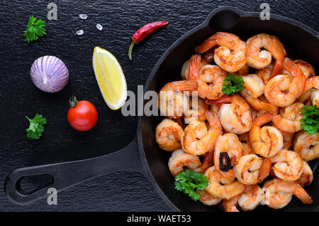 tasty roasted shrimps in a cast iron pan with parsley and garlic, chili, tomato with lemon on black background - Stock Photo