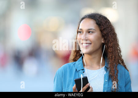 Front view portrait of a mixed race woman listening to music looking at side in the street