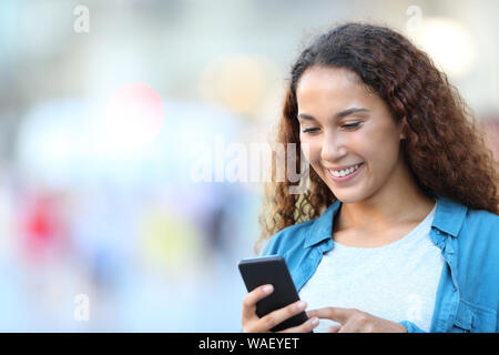 Happy mixed race woman using smart phone walking in the street