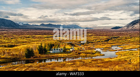 Haukadalur valley in Iceland. Little buildings in peaceful nature environment. Valley landscape sunny autumn day cloudy sky. Amazing beauty of valley. Beautiful landscape with river in valley. - Stock Photo