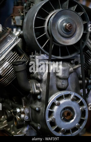 fragment of a semi-assembled old internal combustion engine on a dark background - Stock Photo