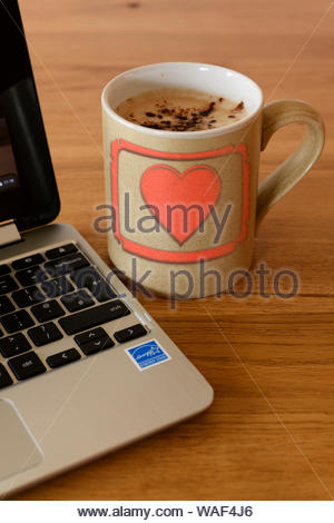 Heart motif on Personal coffee cup next to laptop, Blandford, Dorset, England, UK - Stock Photo