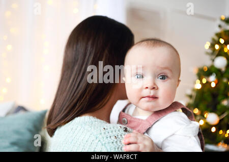 Beautiful happy mother with lher ittle daughter in knit sweater sitting on the background of Christmas interior hugging together and smiling - Stock Photo