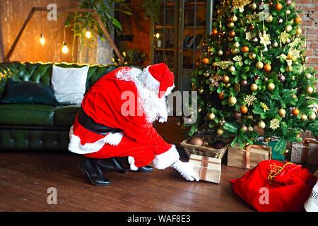 Santa Claus secretly putting gift boxes under the Christmas tree. Xmas - Stock Photo