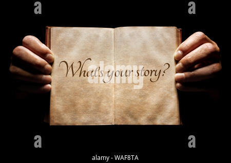 What's your story? hands holding an open book background message - Stock Photo