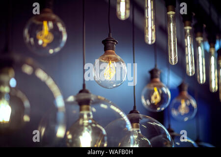 Light bulbs hanging in a row - Stock Photo