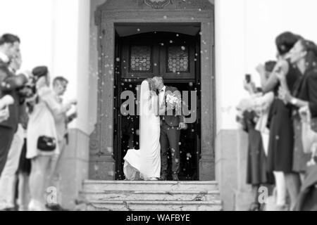 Newlyweds kissing while exiting the church after wedding ceremony, family and friends celebrating their love with the shower of soap bubbles, custom - Stock Photo