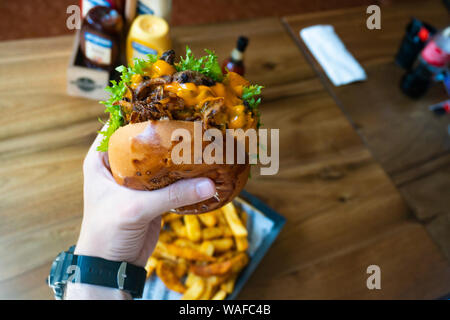 Hands holding fresh delicious burgers with french fries, sauce and beer on the wooden table top view. - Stock Photo