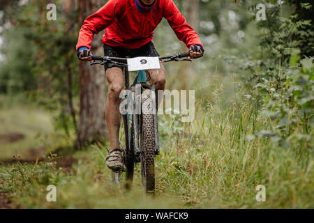 dirty athlete cyclist on mountainbike riding uphill in forest trail - Stock Photo