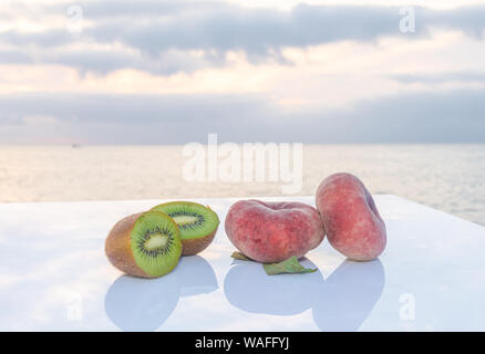 Two delicious flat peaches accompanied by a fresh green kiwi cut in half on a white table - The sea and the blue sky on the background - Fresh fruits - Stock Photo